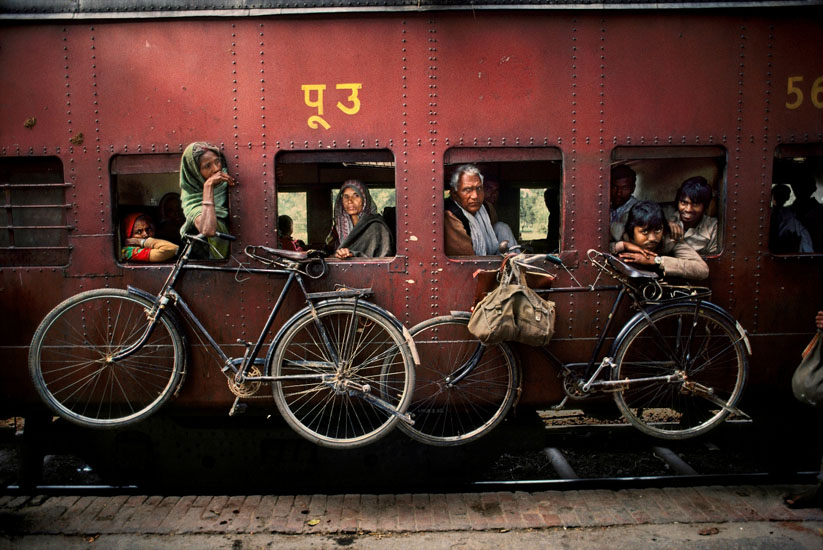 Bicycles on the side of a train, West Bengal, India, 1983 Within a single frame McCurry presents us with four portraits (one could almost say 'character studies') of these travelers. Who knows what each of these individuals are feeling? Where they are going? Who will meet them at the end of their journey? As the bikes hung on the side of the train indicate, maybe for some the journey will continue that little bit further.  Phaidon, Iconic Images, final book_iconic, iconic photographs The Imperial Way_Book Iconic_Book Untold_book final print_UrbanArt'12 retouched_Sonny Fabbri 5/24/2013