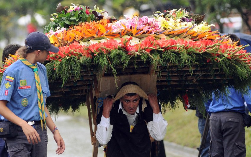 A man carries a flower arrangement on his black during the annual festival of flowers in Medellin, Colombia, Sunday, Aug. 11, 2013. The flower festival is one of the most important events of Medellin and has been celebrated every year since 1957. (AP Photo/Luis Benavides)